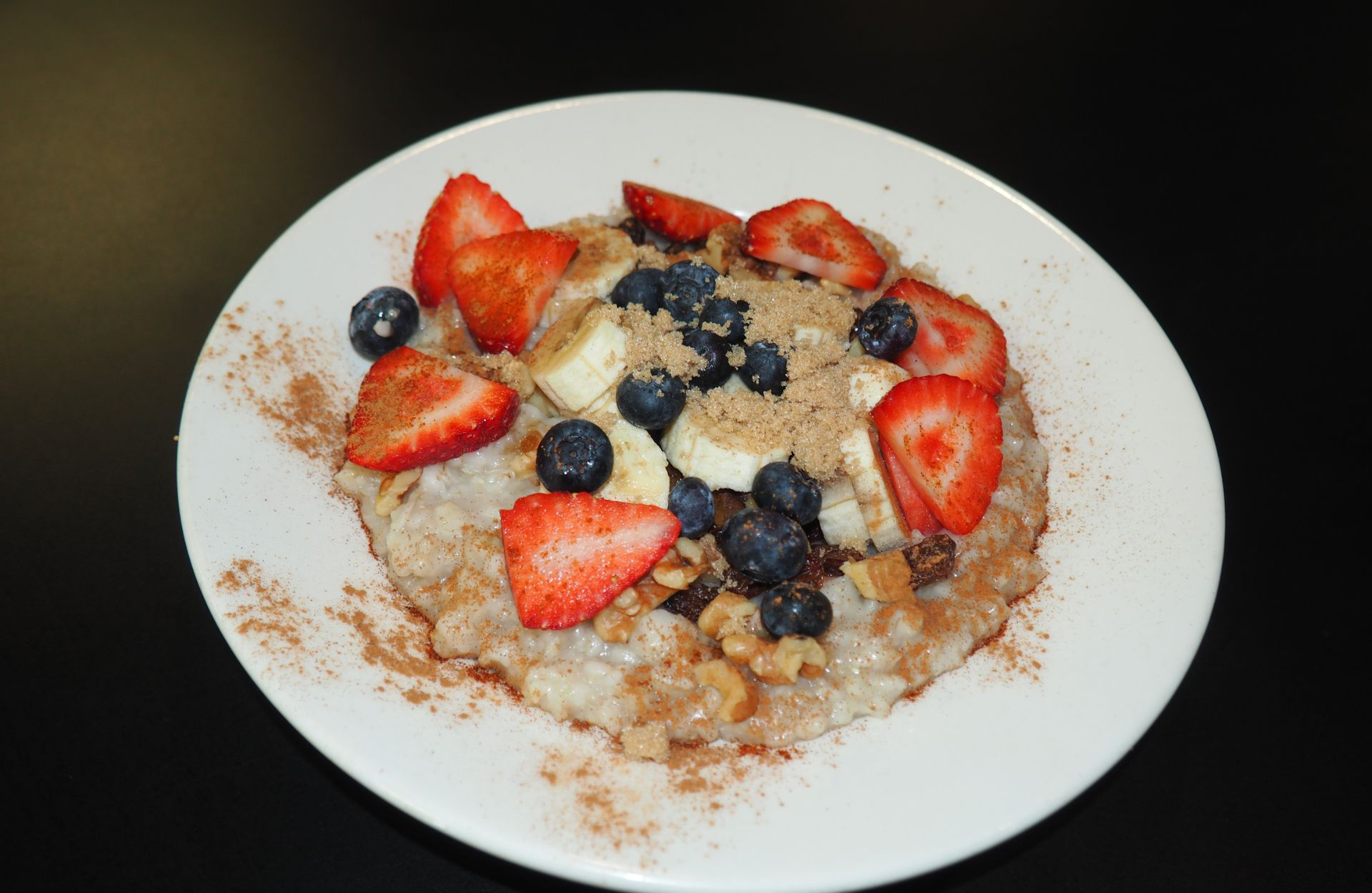 Oatmeal with strawberries, blueberries and bananas with cashews and cinnamon