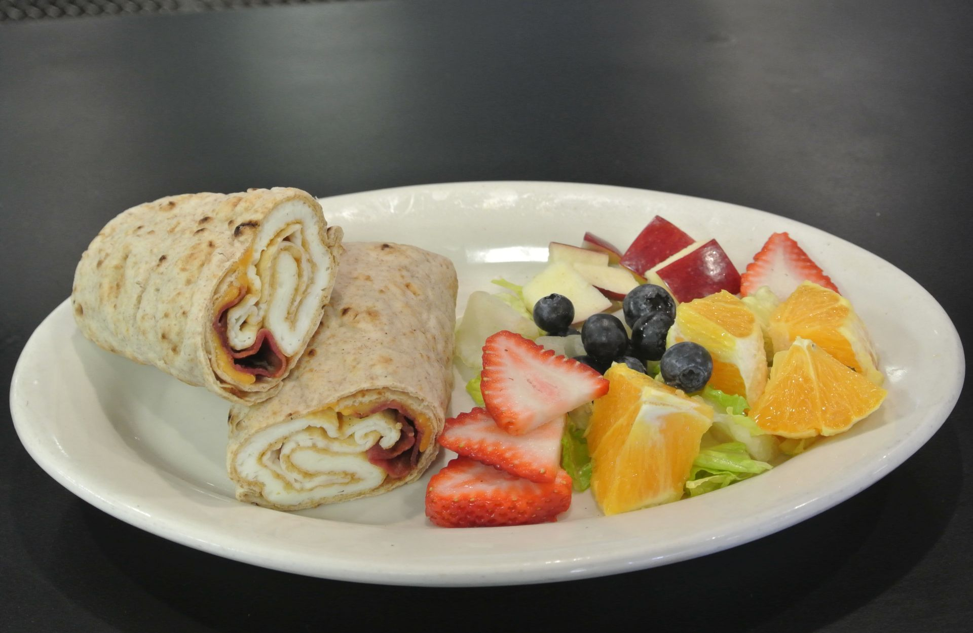 Breakfast burrito with egges and bacon in a wrap with fresh cut fruits