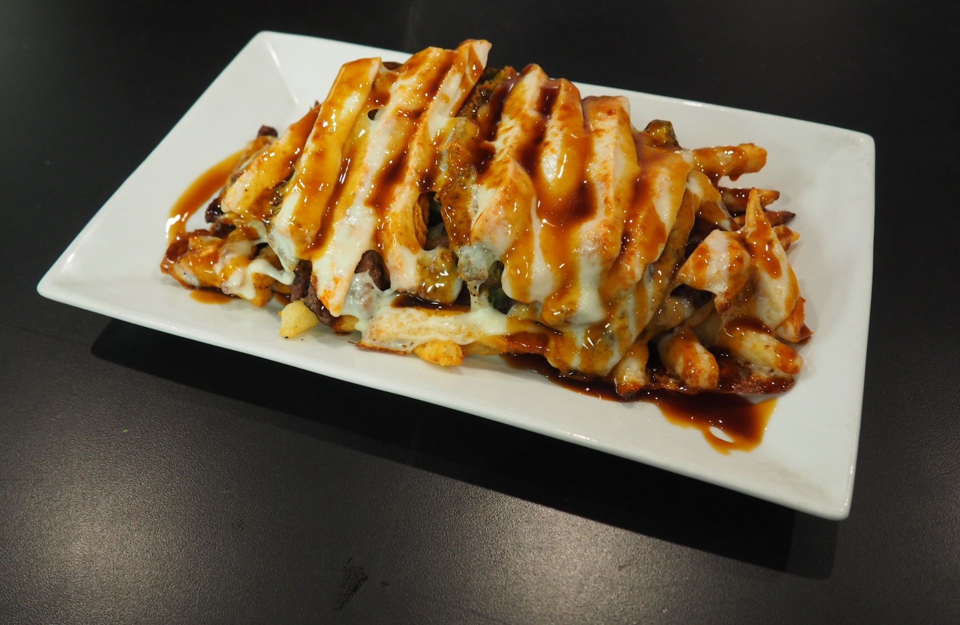 Grilled sliced chicken with cheese and gravy over fries