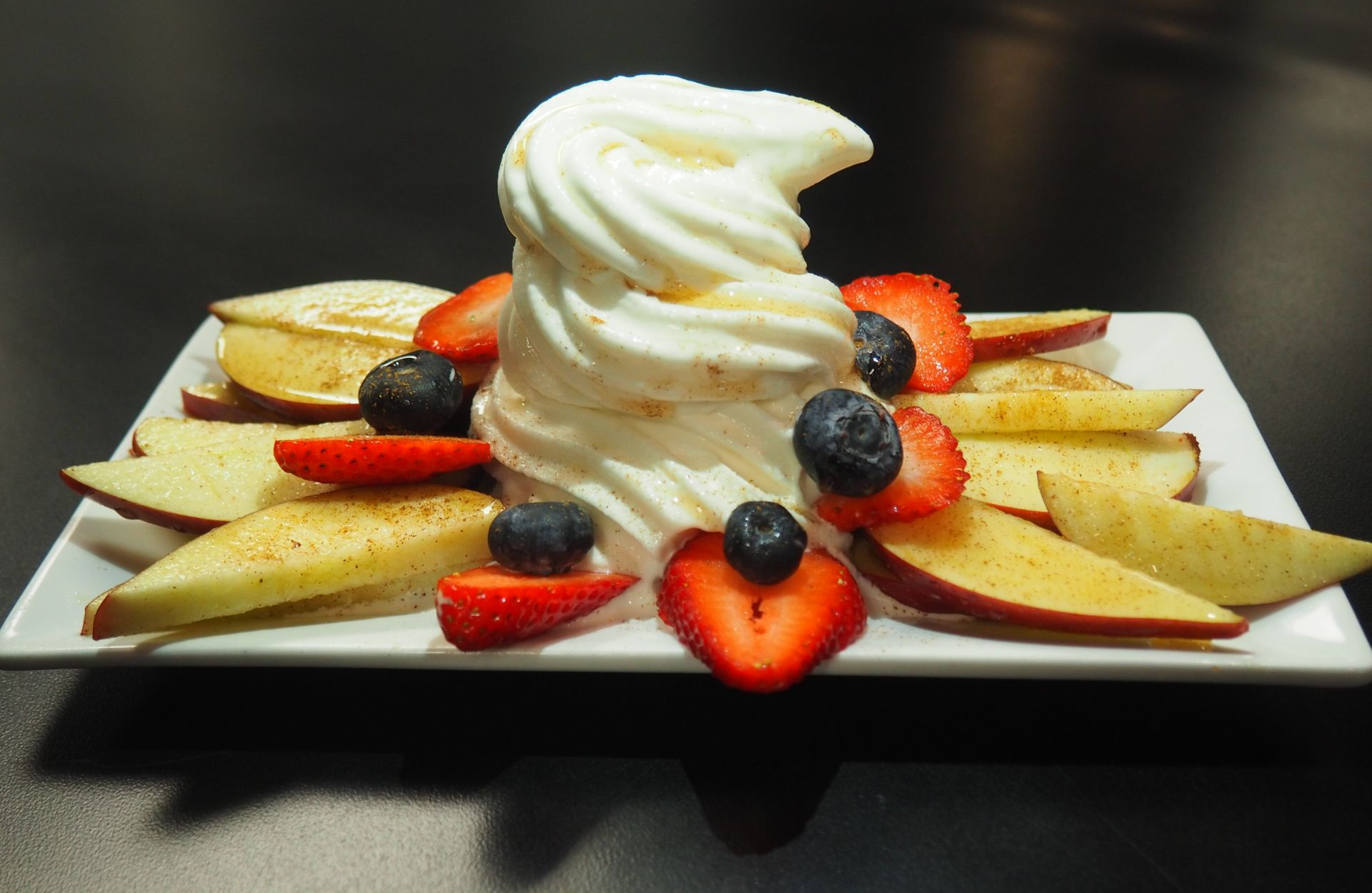 Sliced apples, strawberries and blueberries with frozen yogurt