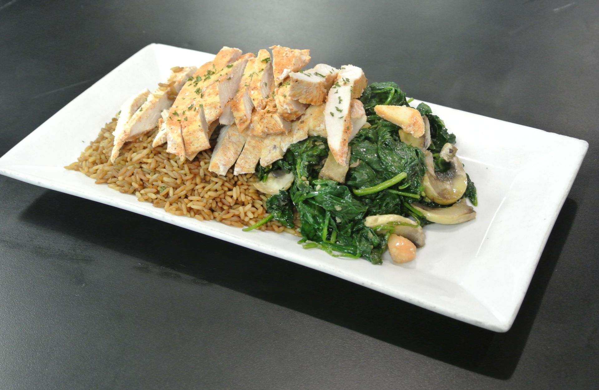 Grilled chicken over brown rice with sauteed spinach and mushrooms