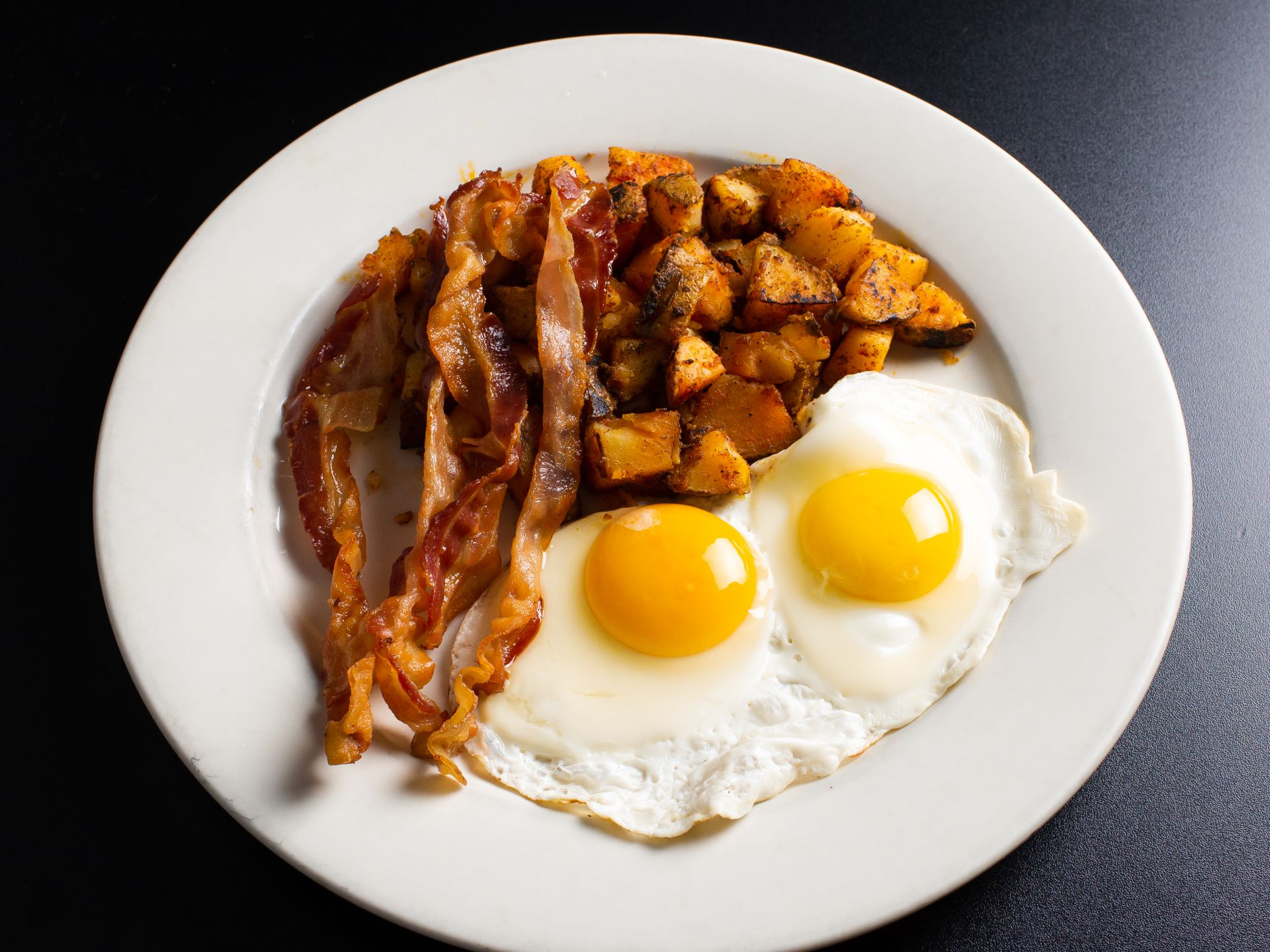 Two fried eggs sunny side up with bacon and potatoes