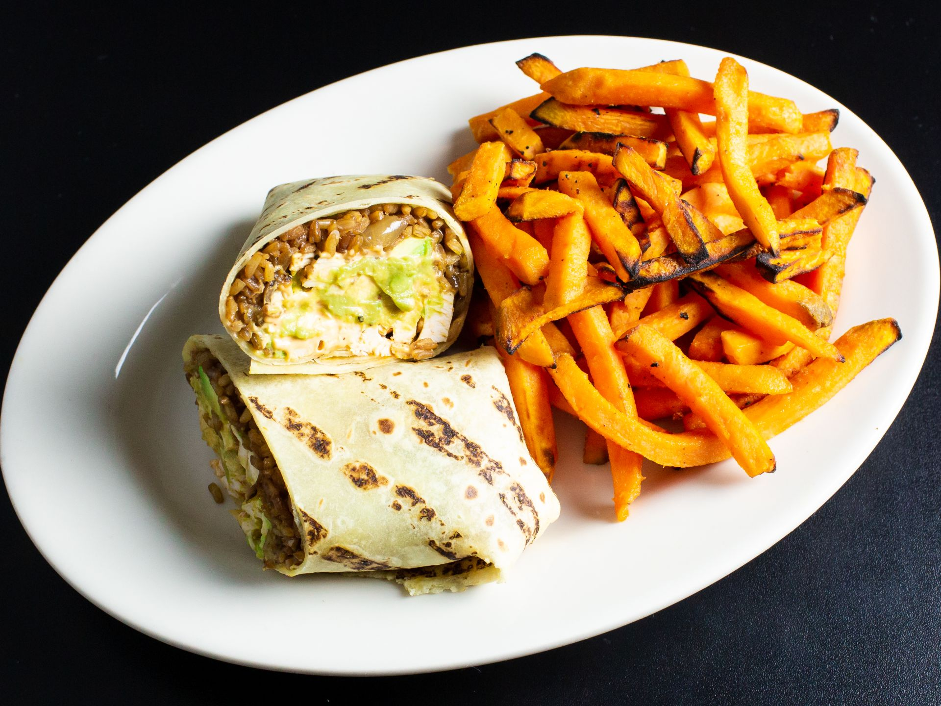 Grilled chicken burrito with avocado and beans and a side of sweet potato fries