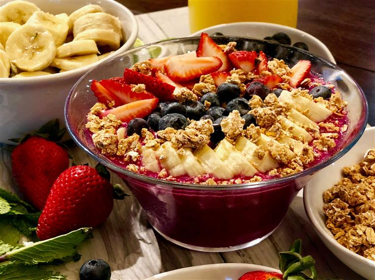 Acai bowl topped with granola, bananas, blueberries, strawberries and honey on a table with a bowl of bananas