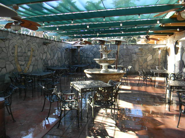 exterior patio area with tables, chairs and space heaters