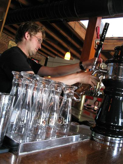 bartender pouring a glass of beer from the tap