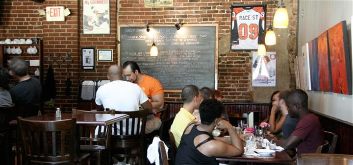 customers eating at tables with a large chalkboard being displayed with daily specials