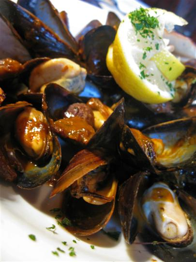mussels in sauce with lemon wedge