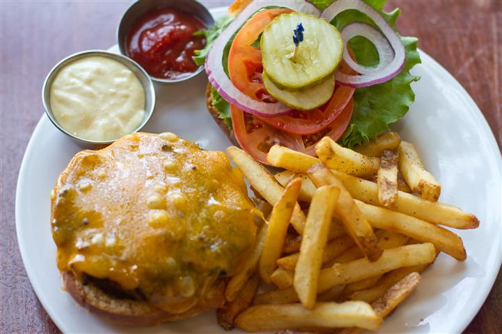 cheeseburger topped with tomato, lettuce, pickles and onions with a side of fries