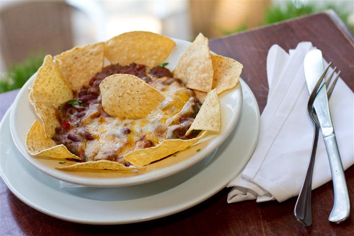bowl of chips and dip covered in cheese