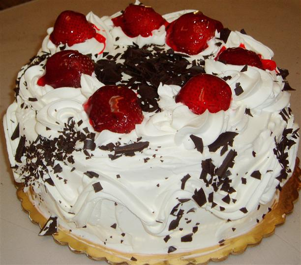 Cake with strawberries, icing, and chocolate sprinkles