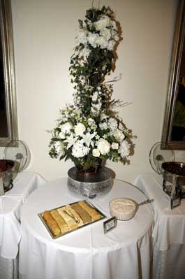 flower arrangement on a table with a plate of appetizers