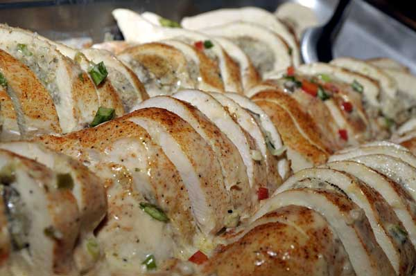 catering display of sliced chicken breasts with herbs