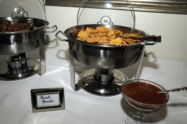 metal catering display of fried raviolis with a side of dipping sauce