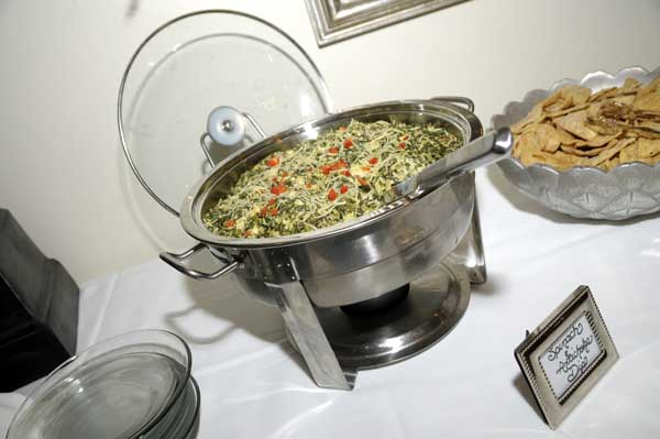 metal catering display of spinach and artichoke dip with a side of chips