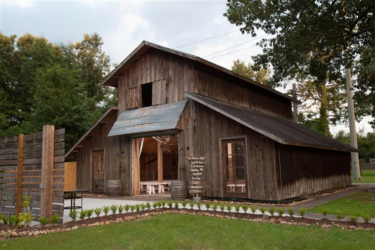 Exterior shot of rustic wood barn, open entrance with wooden benches