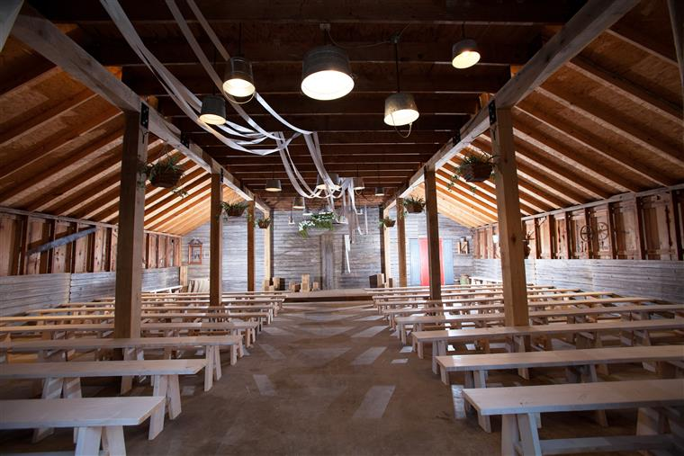Interior of rustic wood barn, white benches, lights on ceiling and stage.