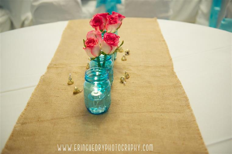 Blue mason jars with pink and white flowers on cloth on white table. Photo credit www.eringuedryphotography.com