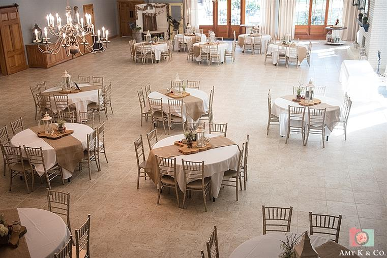 Large room with floor tiles and candlelight chandeliers. Multiple round tables with cloths, centerpieces and chairs.