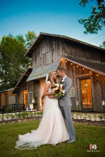 bride and groom taking wedding photos together standing outside a wooden barn