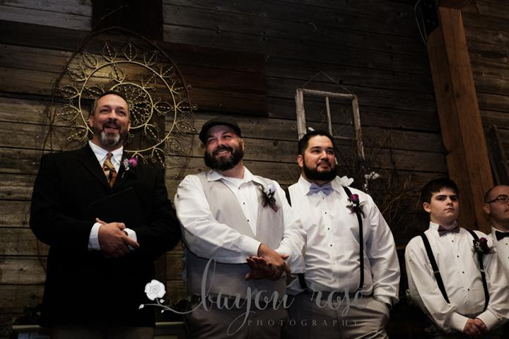 groomsmen smiling with the groom standing at the alter