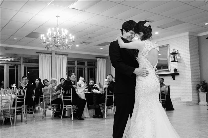 bride and groom taking their first dance together as other watch