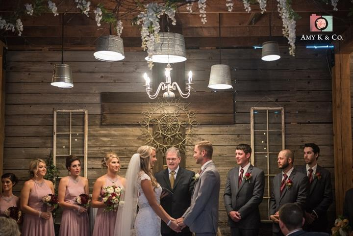 indoor wedding ceremony with the bride and groom at the alter with the wedding party