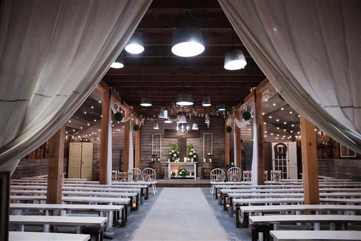 indoor ceremony arrangement with chairs, alter and lighting