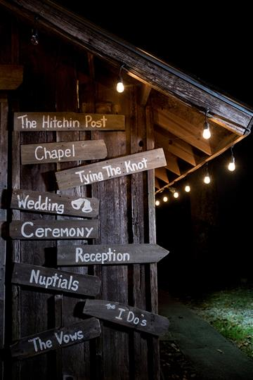 various wood signs hanging on a barn that point to directions around the establishment