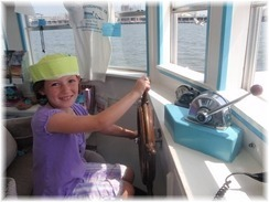 little girl wearing a hat steering the boat