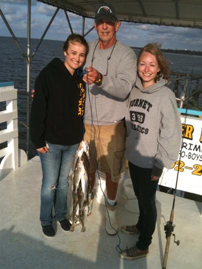 man holding fish with two females standing next to him