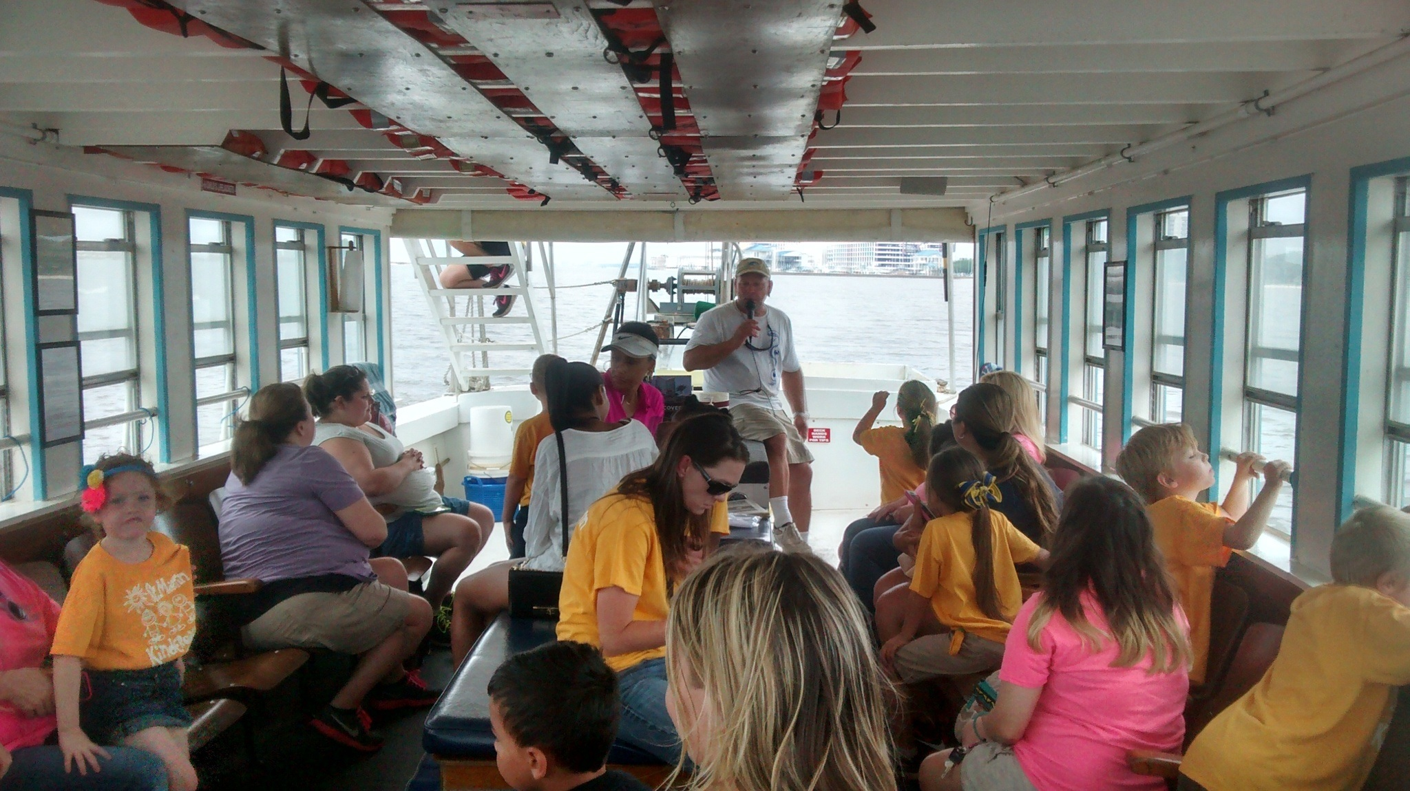 people on boat with man holding microphone giving a tour