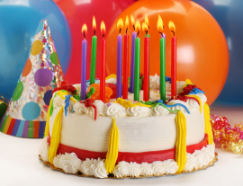 birthday cake with several different colored candles lit