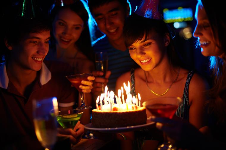 female smiling about to blow out candles on a birthday cake surrounded by friends