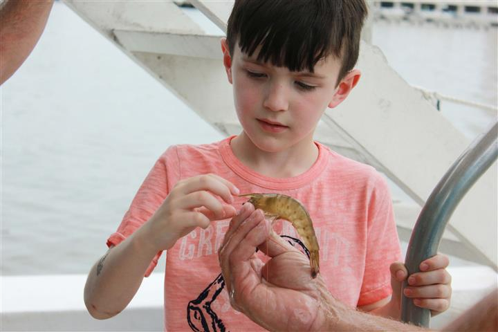 young boy putting bait on hook