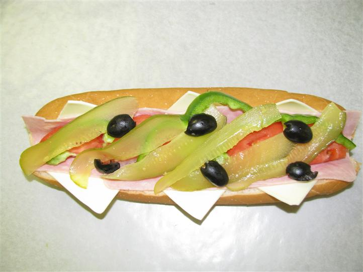 sandwich with pickles, olives, peppers, and deli meat
