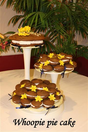 Three different height pastry displays with whoopie pies and floral decorations