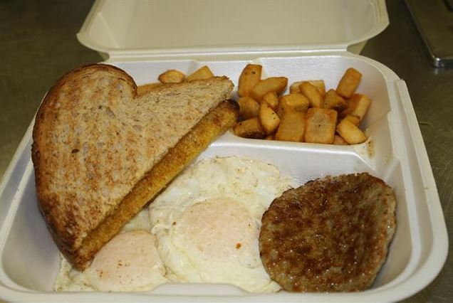 Takeout container with two fried eggs, a sausage patty, homefries and two slices of toast