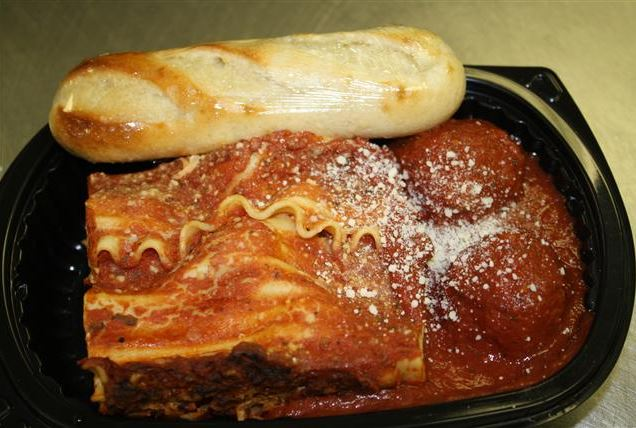 Takeout container with a piece of lasagna, two meatballs topped with parmesan cheese and a side of bread