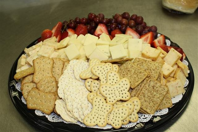 Platter with crackers, assorted cheeses, strawberries and red grapes