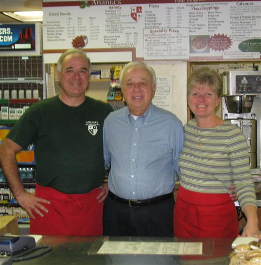 Three staff members smiling with their arms around each other behind the counter