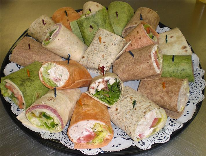 Platter with different wraps filled with cheese, deli meats and lettuce Available on white, wheat, spinach or tomato basil wraps