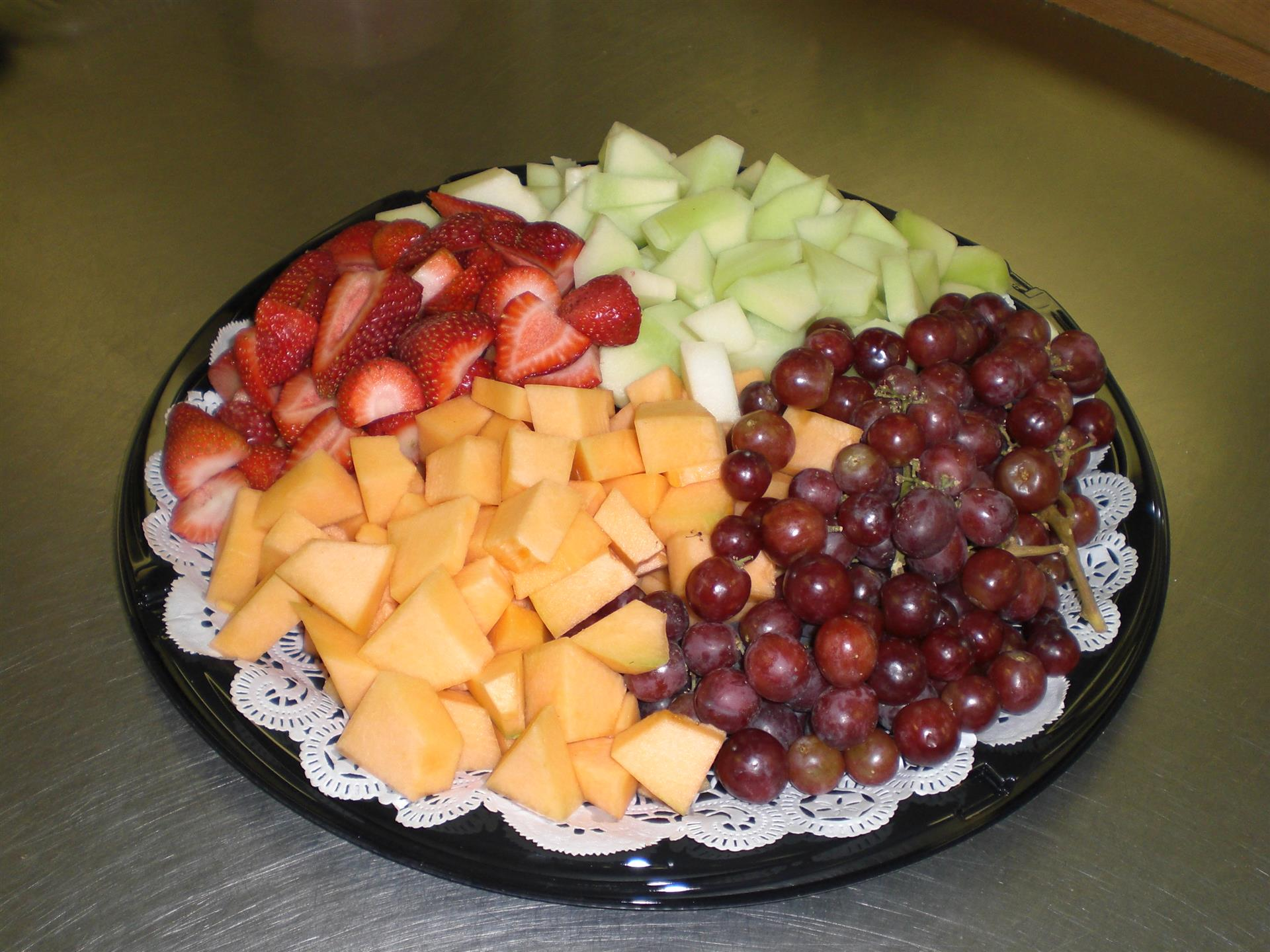Fruit platter with canteloupe, red grapes, strawberries and honey dew