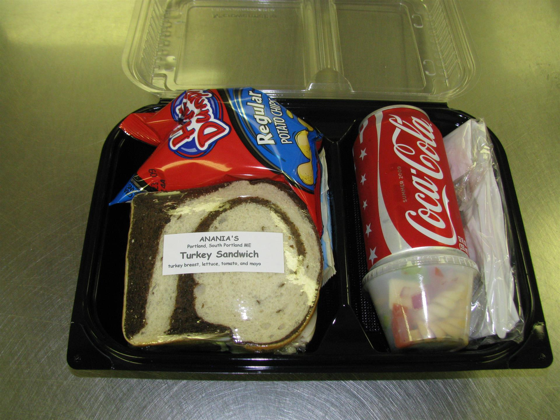 Lunch container with a turkey sandwich, bag of chips, a can of Coca Cola and a small cup of pasta salad