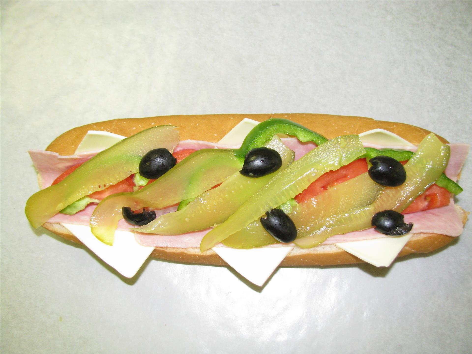 Sub with cheese, deli meats, green peppers. olives and pickles on top