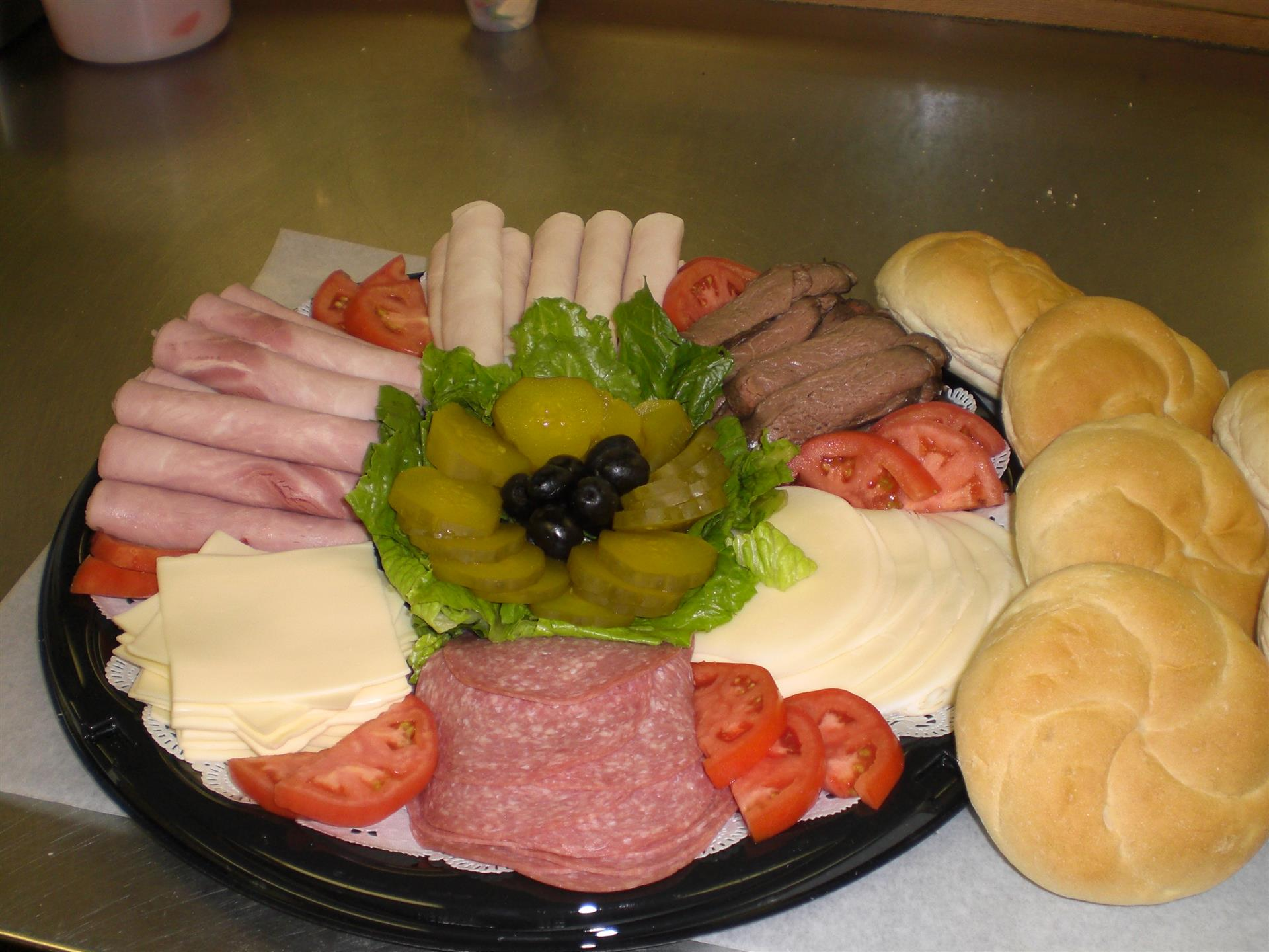 Deli platter with deli meats, cheese, tomatoes and pickles and rolls on the side