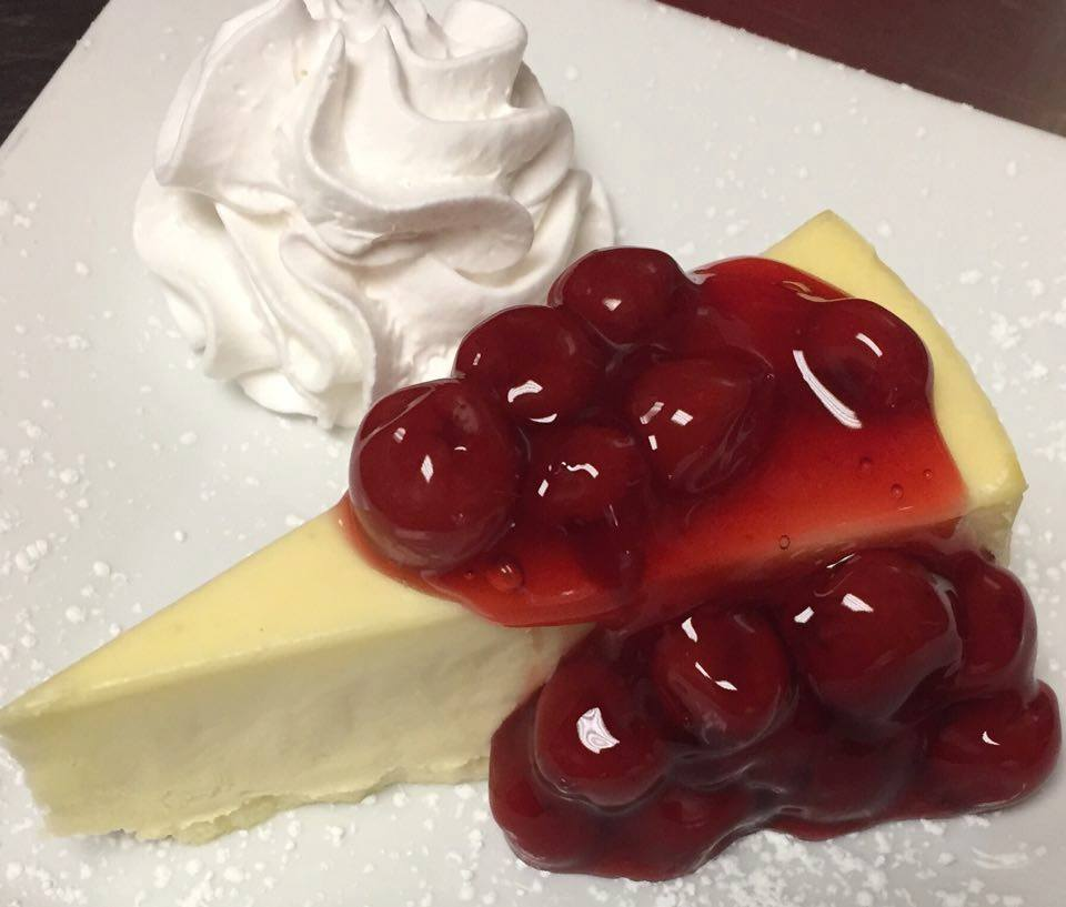 Slice of cheesecake topped with cherries and whipped cream