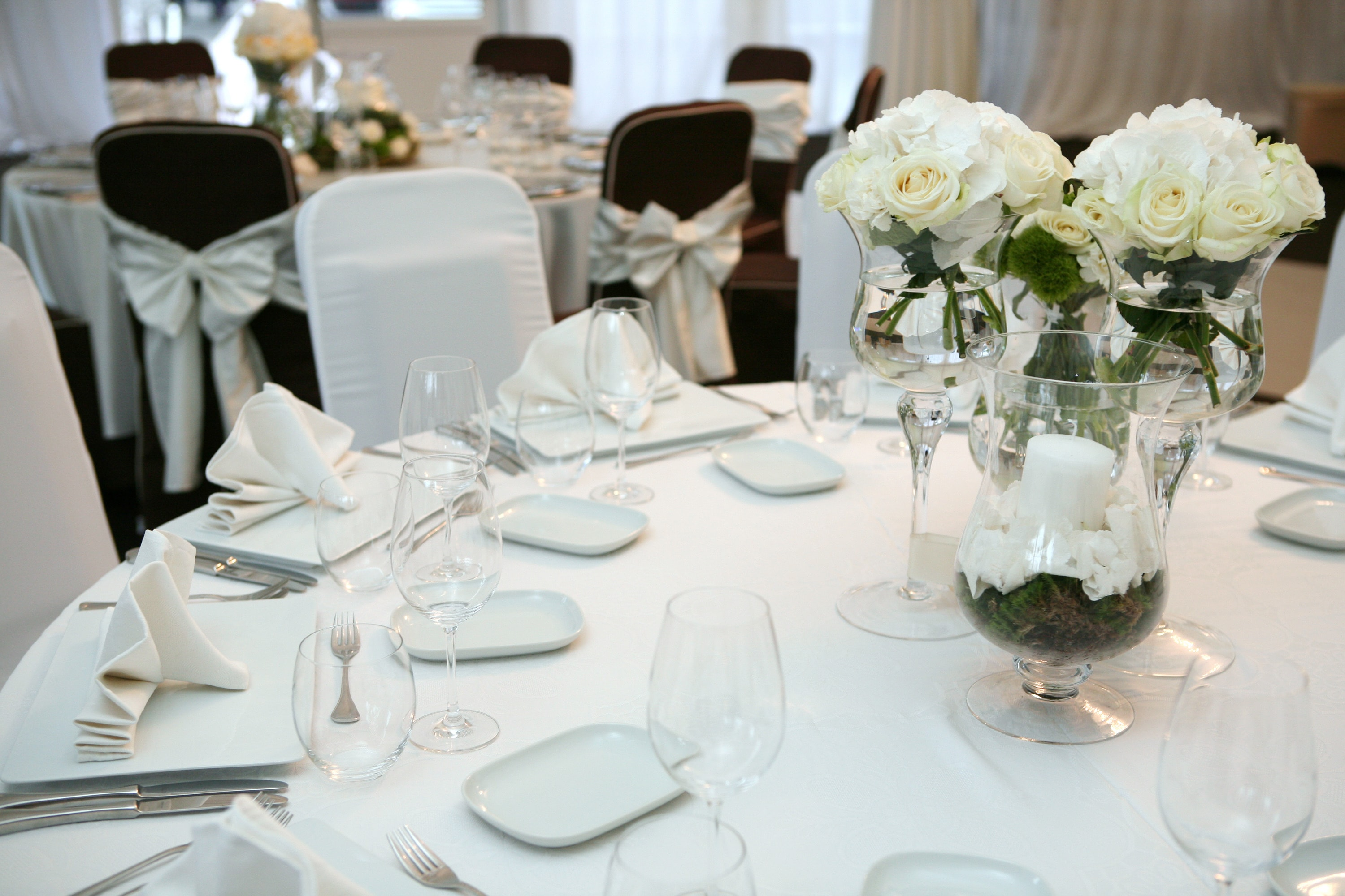 table setting with white table cloth, cloth napkins and fresh flower centerpeices