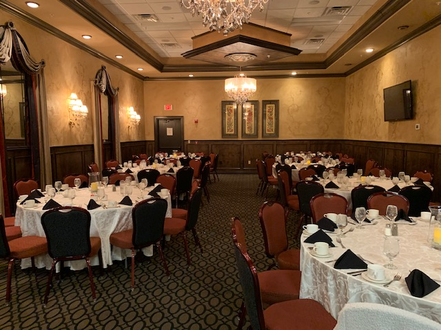 banquet room set up with tables chairs white table cloths warm lighting