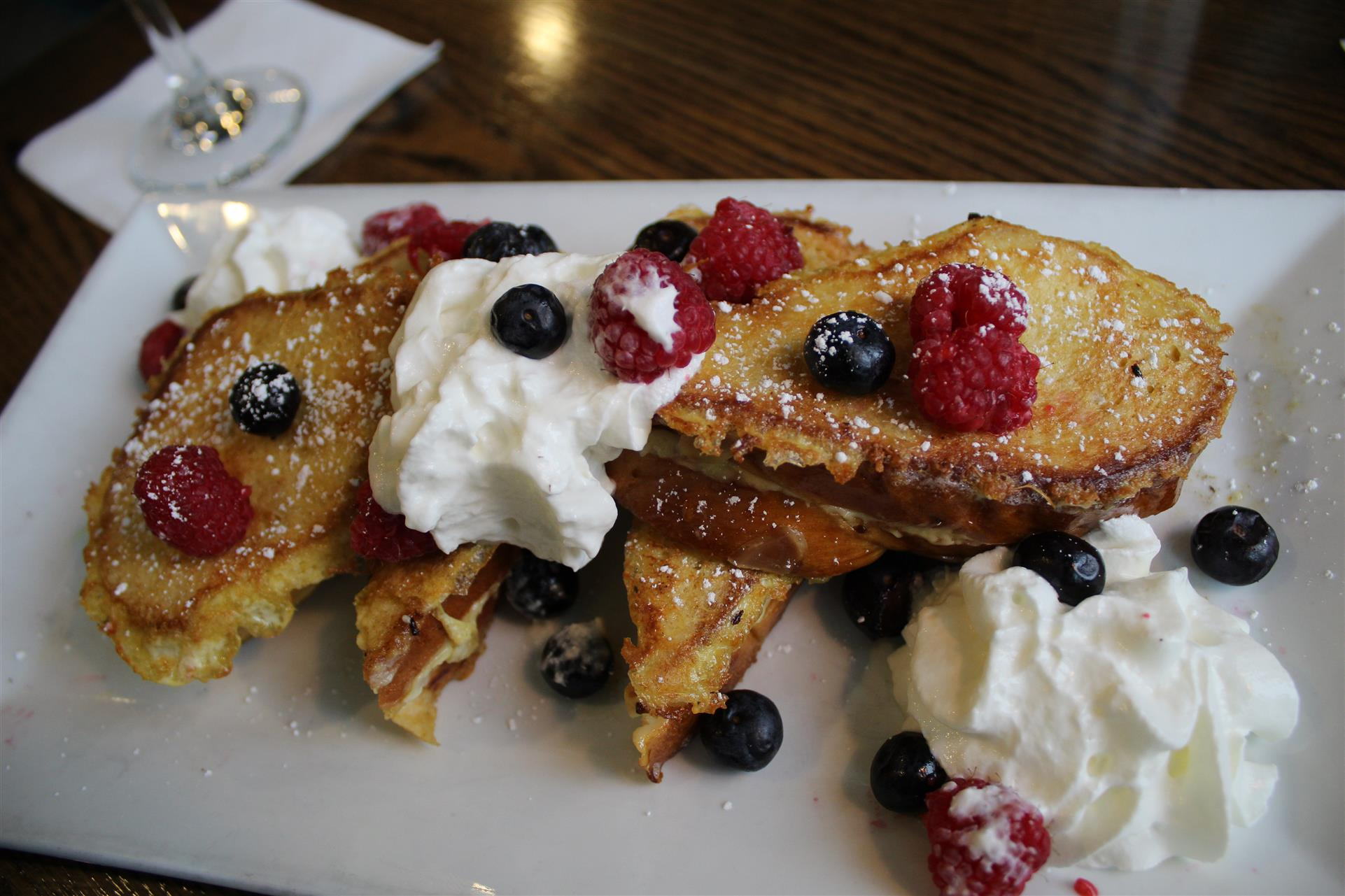 close up of french toast with whipped cream, raspberries and blueberries
